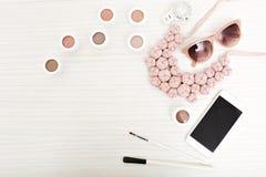 Elegancki wizerunek kobiety s akcesoria odizolowywający nad lekki drewniany tło na Różowa ornamentacja, kolia, telefon obraz royalty free
