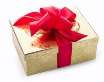 Elegancki złocisty prezent z czerwonym dekoracyjnym łękiem Fotografia Royalty Free