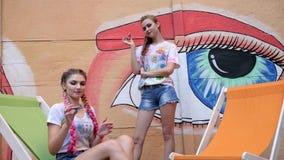 Eleganckie dziewczyny pokazuje sztuczkę z kądziołkami na tle graffiti, nastolatków zabawka dla stres ulgi wir dalej zbiory
