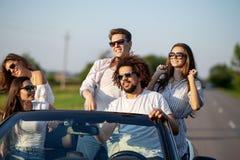 Eleganckie młode dziewczyny i faceci w okularach przeciwsłonecznych ubierających w biali ubrania siedzą w czarnym kabriolecie na  zdjęcia stock