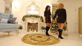 Eleganckie młode kobiety doceniają stroje each inny ono uśmiecha się w dekorującym żywym pokoju z choinką i grabą zbiory