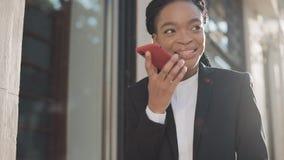 Eleganckiego afro bizneswomanu dosłania głosu audio wiadomość na telefonie komórkowym przy plenerowy opowiadać mobilny asystent B zdjęcie wideo