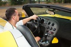 Eleganckiego mężczyzna sterowniczy żółty cabrio zdjęcia stock