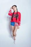 Eleganckiego modnisia azjatykcia dziewczyna patrzeje kamerę odizolowywającą na popielatym w amerykańskim patriotycznym stroju Obrazy Royalty Free