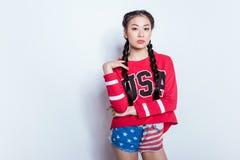 Eleganckiego modnisia azjatykcia dziewczyna w amerykańskim patriotycznym stroju pozuje kamerę odizolowywającą na popielatym i pat Obraz Stock