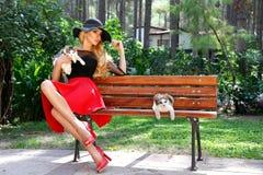 Eleganckiej blondynki kobiety kobiety wzorcowej jest ubranym wiosny odzieżowy i kapeluszowy obsiadanie na ławce w normie Obraz Stock