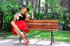 Eleganckiej blondynki kobiety kobiety wzorcowej jest ubranym wiosny odzieżowy i kapeluszowy obsiadanie na ławce w normie Zdjęcia Royalty Free