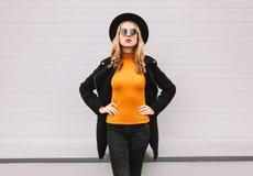 Eleganckiej młodej kobiety czerni stylu wzorcowi jest ubranym ubrania, żakiet, round kapelusz, pozuje na miasto ulicie fotografia stock