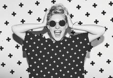 Eleganckiej mody seksownej blondynki zła szalona dziewczyna trzyma jej głowę w czarnej koszulce rockowym okulary przeciwsłoneczni Fotografia Stock