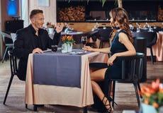 Elegancko ubierająca para przystojna elegancka samiec, powabna brunetki kobieta i rozmowy siedzi wpólnie podczas - obrazy royalty free