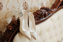 Elegancy wedding shoes of bride with brilliant brooch on the bed Stock Images