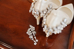 Elegancy wedding shoes of bride with brilliant brooch and earrin Stock Images