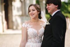 Elegandbruid in mooie witte huwelijkskleding met knappe bruidegom in het park Groene Achtergrond stock afbeelding