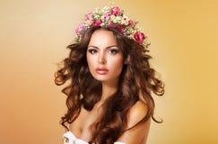 Elegans. Flott förtjusande dam med blommor och flödande hår royaltyfri bild