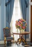 Elegansfåtölj- och blommabukett på tabellen Arkivfoto