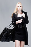 Elegant. Woman in elegant black dress and topcoat with handbag Stock Photography