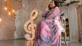 Elegant adult woman in a lilac dress sitting in a Chair. Luxurious interior stock video footage