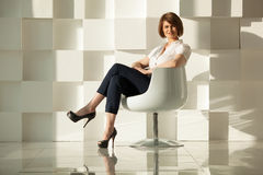 Elegant adult woman sitting in chair against of white modern wall Stock Photography
