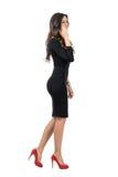 Elegant affärskvinna som går, medan tala på mobiltelefonen som bort ser arkivfoton