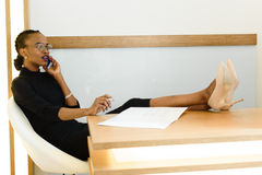 Elegant African or black American business woman, wearing glasses, sitting with legs on table Royalty Free Stock Photo