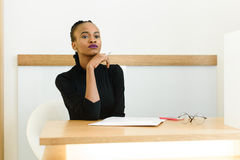 Elegant African or black American woman holding chin with hand thinking and looking away at desk in office.  stock photography