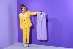 elegant Afrikaans Amerikaans meisje die in geel kostuum modieus purper vest, op in ultra houden stock afbeeldingen