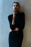 Elegant afrikan eller amerikansk kvinna för svart som ner ser med handen under hakan på grå bakgrund Royaltyfri Foto