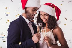 Couple with New Year mood. Elegant Afro American couple in Santa hats clinking glasses of champagne and smiling, on white background Royalty Free Stock Image