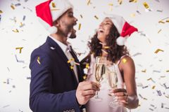 Couple with New Year mood. Elegant Afro American couple in Santa hats clinking glasses of champagne and smiling, on white background Stock Images