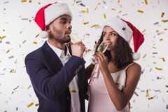 Couple with New Year mood. Elegant Afro American couple in Santa hats drinking champagne, on white background Stock Photography