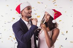 Couple with New Year mood. Elegant Afro American couple in Santa hats drinking champagne, on white background Stock Photo