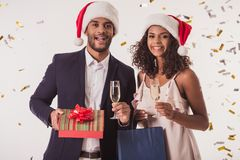 Couple with New Year mood. Elegant Afro American couple in Santa hats holding presents and glasses of champagne, looking at camera and smiling, on white Stock Photo