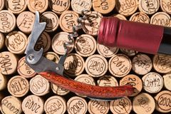 Elegant, already open corkscrew and the bottleneck of a bottle of wine. Lie on a background of many different vintage corks stock image