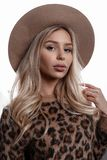 Elegant amazing young woman in a luxurious beige hat with lips with brown eyes with curly blond hair in a leopard sweater. On a white background in the room stock images