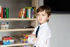Elegant angekleidet in einem weißen Hemd und kleinen einem Jungen der Bindung Stockfotografie