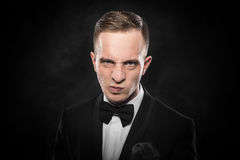 Elegant angry young man in suit looking frowning. Royalty Free Stock Image