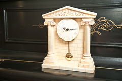Elegant antique clock. Clock with Greek temple. Marble clock on black piano Royalty Free Stock Photography