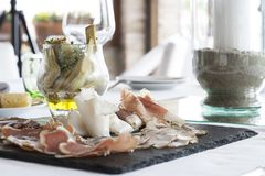 Elegant appetizer on black slate plate. Mixed salami and artichokes in oil stock photos