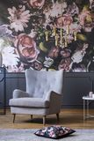 Elegant armchair, flower print on a wall and pillow on a floor in a daily room interior. Real photo Stock Image
