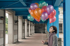 Elegant Asian beauty holding balloons under bridge Stock Photo