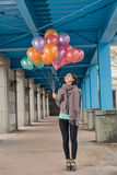 Elegant Asian beauty holding balloons under bridge Stock Photos