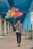 Elegant Asian beauty holding balloons under bridge Royalty Free Stock Photography