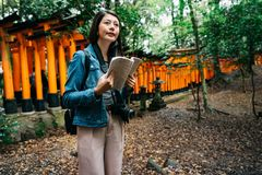 Elegant asian photographer holding her guidebook. Elegant asian photographer standing near the Torii and holding her guidebook. female lens man in green forest stock photos