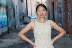 Elegant Asian woman in dark urban alley way  with copy space Royalty Free Stock Photography