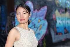 Elegant Asian woman in dark urban alley way isolated with copy space Royalty Free Stock Photo