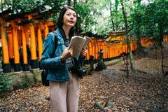 Elegant asiatisk fotograf som rymmer hennes resehandbok arkivfoton