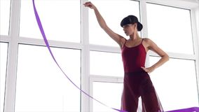 Elegant athlete performs gymnastic exercises in the training hall, lady dances. A young gymnast coaches dance elements with a ribbon, a lady dances a modern stock footage