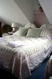 An elegant attic double room. An elegant attic room with a double bed stock photography
