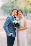 Elegant attractive bride and groom posing outdoors in the park. Newlyweds portrait shot Royalty Free Stock Image