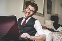 Elegant attractive fashion hipster man using notebook Stock Photography